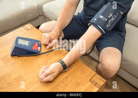 Blood pressure measurement, with an automatic upper arm blood pressure monitor, Germany - Stock Photo