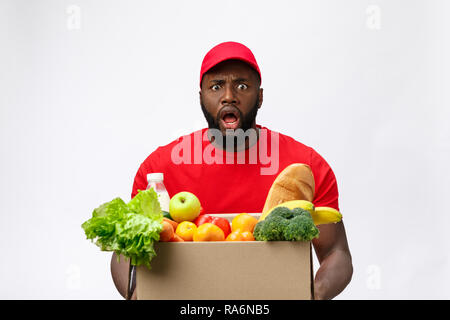 Young african american man holding grocery box in hands with shocking face. Isolated over Grey background. - Stock Photo