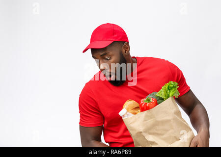 Young african american man holding grocery package in hands with shocking face. Isolated over Grey background. - Stock Photo