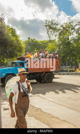 man carrying plastic bottles for recuban workers being transported to their pace of work in the back of a heavy goods truck in Havana, Cuba, Caribbean - Stock Photo