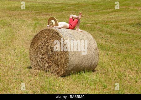 Boy lying on a bale of straw, Germany - Stock Photo