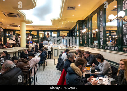 Famous Madrid chocolate bar San Gines, Chocolatería San Ginés, packed in winter with people eating churros and drinking hot chocolate. Madrid Spain. - Stock Photo