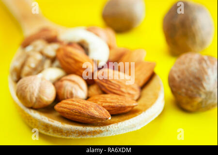 Almonds, Hazelnuts, Walnuts, Cashew Nuts in a Wooden Spoon, and Three Whole Walnuts Isolated on Yellow Background. Healthy Organic Snack, Breakfast, F - Stock Photo
