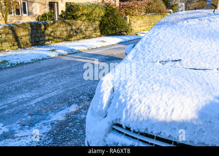 Close-up of snow covered car parked on icy main street of small rural village on freezing cold snowy winter day - Timble, North Yorkshire, England, UK - Stock Photo