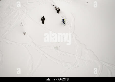freerider snowboarder down the steep slope of white snow and trees in the mountains of the Caucasus - Stock Photo