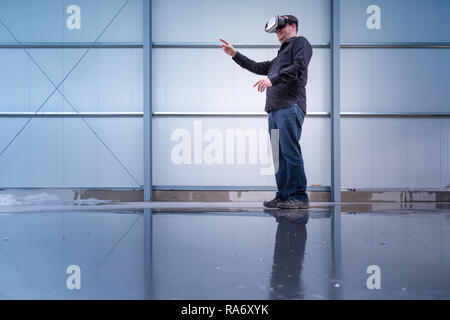 Construction worker standing at indoor construction site wearing vr eyeglasses or goggles, bright environment with space for your copytext or imagery projection - Stock Photo