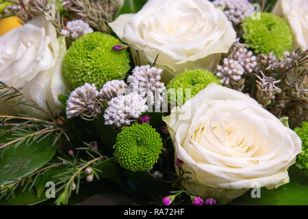 Beautiful bouquet of flowers with white ranunculus buttercup, green carnation and small purple and white flowers still life - Stock Photo