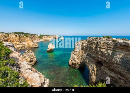 Turquoise sea, Praia da Marinha beach, rugged rocky coast of sandstone, rock formations in the sea, Algarve, Lagos, Portugal - Stock Photo