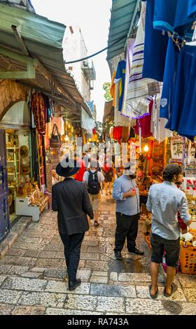 Street scene, people with traditional Jewish clothes in a narrow alley, shopping alleyway, old town, Jerusalem, Israel - Stock Photo