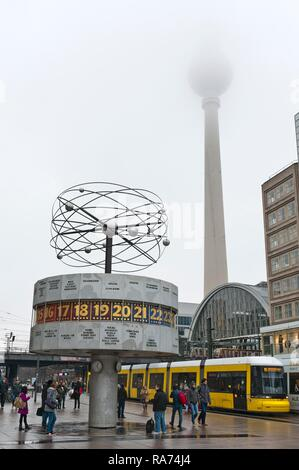 World time clock, yellow tram train, TV tower in the fog, Alex, Alexanderplatz, Berlin Mitte, Berlin, Germany - Stock Photo