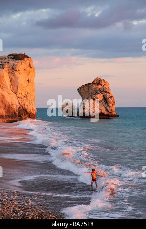 Paphos, Cyprus - November 24, 2018: A boy plays at the beach at the Petra tou Romiou rocks, in Paphos, Cyprus. The beach is considered to be Aphrodite - Stock Photo