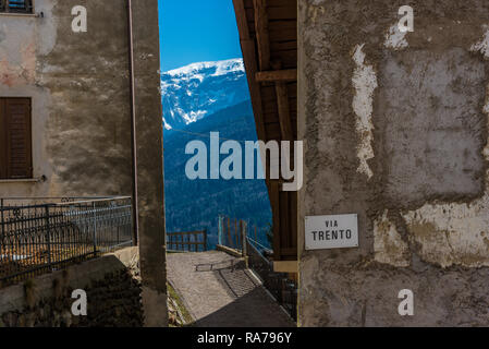Mountain view form Via Trento - narrow street, alley in Termenago, small italian village in municipality of Pellizzano, Trento, Italy. - Stock Photo