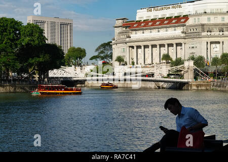A man relaxing near Boat Quay by the Singapore River, Singapore; b/g: Cavenagh Bridge and (right) Fullerton Hotel, located in the former G.P.O. bldg. - Stock Photo