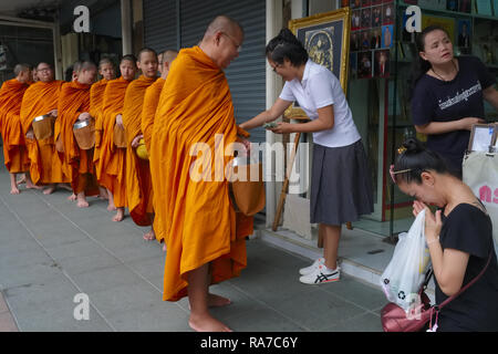 During their morning alms round, monks from Wat Mahathat in Bangkok, Thailand, collect food and small sums of money from shopkeepers near their temple - Stock Photo