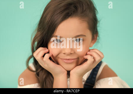 Little girl with smile on adorable face on blue background. Child pose with hands at young healthy face skin. Skincare, health, youth. Beauty, look, hairstyle, punchy pastel - Stock Photo