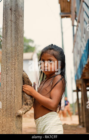 Boca de valeria, Brazil - December 03, 2015: child girl selling sloth in village. Earning money and lifestyle concept. Poverty and childhood - Stock Photo