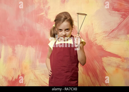 Girl cook with metal potato masher in red chef apron posing on colorful abstract wall. Cooking utensils concept. Child and childhood - Stock Photo