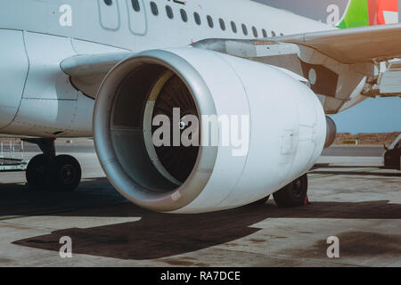 Turbine of passenger jet that waiting for departure in airport in warm afternoon light. - Stock Photo