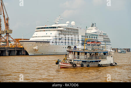 Santarem, Brazil - December 02, 2015: ship floating on sea and Seven Seas Navigator cruise liner in dock on grey sky background. Luxury lifestyle concept. Tourist destination and travelling - Stock Photo