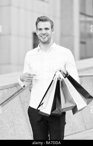 Man formal clothes carry shopping bags. Guy happy carry bunch shopping bags. Profitable deals on black friday. Man hold lot paper bags packages after shopping in mall. Black friday sale concept.