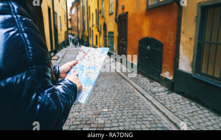 Travel Lifestyle. Woman traveler with map in hand on the streets of Stockholm