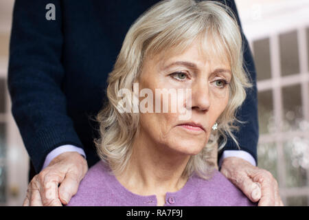 Confused Senior Woman Suffering With Depression And Dementia Being Comforted By Husband - Stock Photo