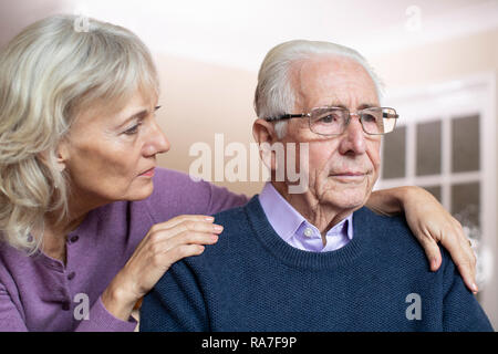 Confused Senior Man Suffering With Depression And Dementia Being Comforted By Wife - Stock Photo