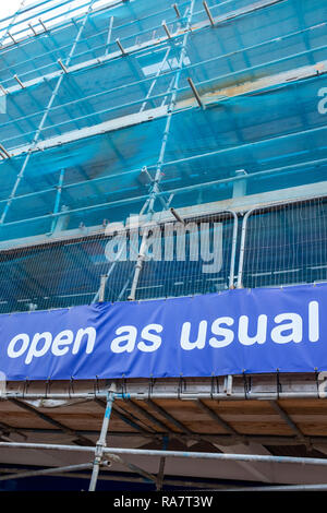 Shop in scaffolding with open as usual sign - Stock Photo