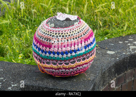 Stone ball on a wall, embroidered with wool, guerrilla knitting (composed of guerrilla - by span guerrilla for 'small war' - and English Knitting for  - Stock Photo