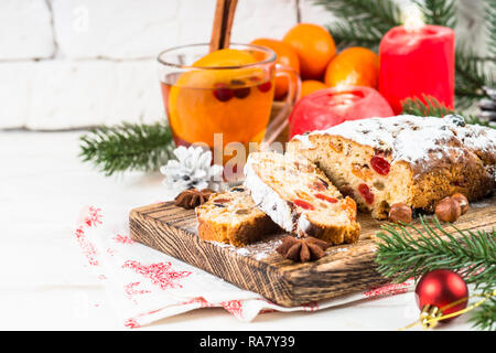 Stollen traditional Christmas ftuitcake with dried fruits and nuts on white table. Christmas food. - Stock Photo