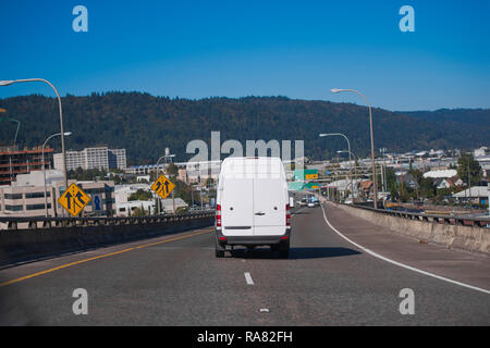 White popular compact comfortable commercial useful economical small business or cargo delivery mini van running on the wide highway in industrial are - Stock Photo