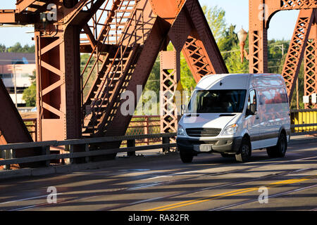 White popular compact comfortable commercial useful economical small business or cargo delivery mini van running on the Broadway bridge in Portland to - Stock Photo