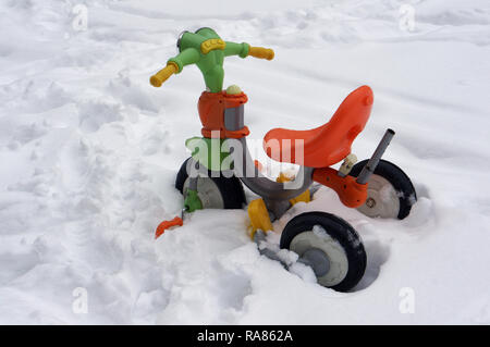 In the deep snow is a forgotten children's  no name  mass production bike - Stock Photo
