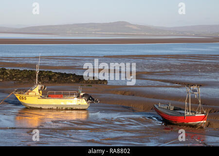 Two small fishing boats, one yellow and one red, on mud at low tide on New Year's Day by the Stone Jetty at Morecambe, Lancashire, United Kingdom. - Stock Photo