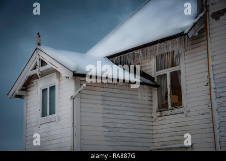 Winter snowfall and icicles on a Norwegian house, Finnsnes, Norway. - Stock Photo