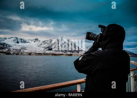 Photographing the coast from on board the Hurtigruten coastal steamer, Norway. - Stock Photo