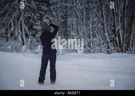 Female photographer capturing winter snows at Finnsnes, Norway. - Stock Photo
