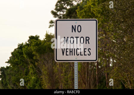 Close up of a no motor vehicles sign in front of trees. - Stock Photo