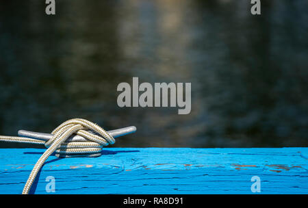 White flexible braided mooring rope from boat side firmly knotted on the reliable strong metal bracket in silver color reinforced on the edge of blue  - Stock Photo