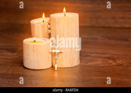 Silver rosary with Jesus on the Candle at wooden table,religion concept,vintage style. - Stock Photo