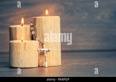 Silver rosary with Jesus on the Candle at wooden table,religion concept,vintage style with split toning. - Stock Photo