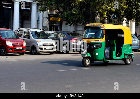 Auto rickshaw riding away on Indian roads in Connaught Place, Delhi, India - Stock Photo