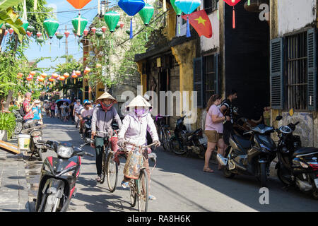 Typical street scene with local women riding bicycles in narrow street in old quarter of historic town. Hoi An, Quang Nam Province, Vietnam, Asia - Stock Photo