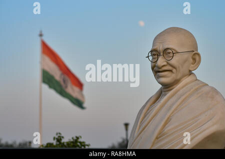 Bust of Gandhi statue with Indian tricolor in the background in Connaught Place, Delhi, India. Mahatma Gandhi is the Father of nation. - Stock Photo
