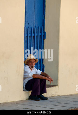 Cuban Man sitting in a doorway, smoking a cigar, Trinidad, Cuba - Stock Photo