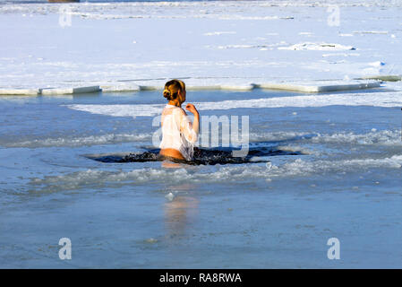Winter sport. A woman swims in the winter river covered with ice during the holiday of Epiphany. Hardening - Stock Photo