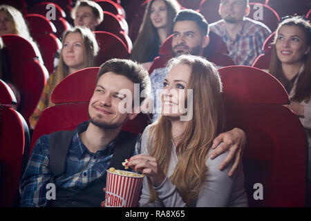 Couple sitting together in cinema, watching comedy or romantic movie. Handsome man hugging beautiful girlfriend sitting near while movie review. Concept of leisure and free time. - Stock Photo
