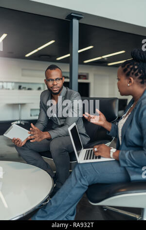 Two african business people talking seriously with hand gestures during a meeting using their laptop and tablet - Stock Photo