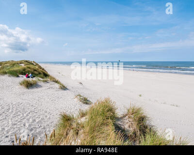 People sitting together on sand dune looking over beach and North Sea on West Frisian island Ameland, Friesland, Netherlands - Stock Photo