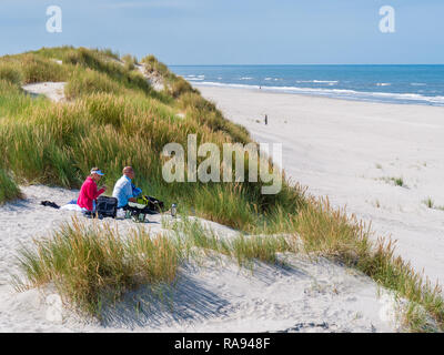 People having picnic on sand dune looking over beach and North Sea on West Frisian island Ameland, Friesland, Netherlands - Stock Photo
